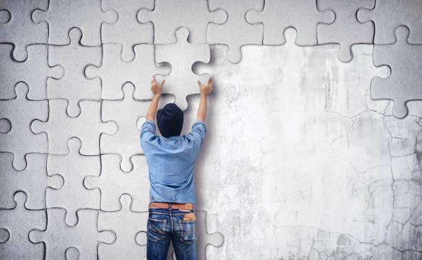 Mann, der ein Rätsel an der Wand. leere Wand mit Platz für text – Foto