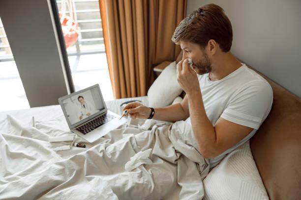 hombre haciendo una videollamada a su médico - telehealth fotografías e imágenes de stock