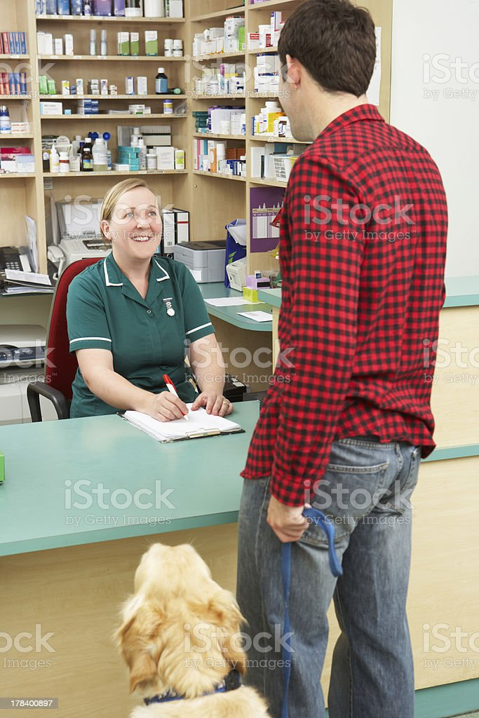 Man Making Appointment At Reception Of Veterinary Surgery stock photo
