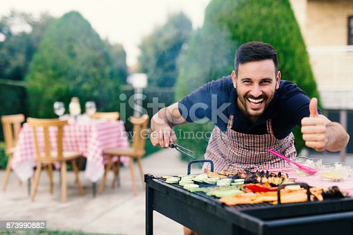 istock Man making barbecue in his backyard 873990882