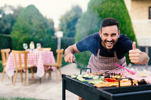 istock Man making barbecue in his backyard 873990882