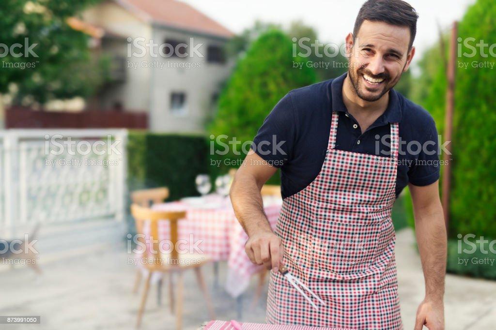Man making barbecue in his backyard stock photo