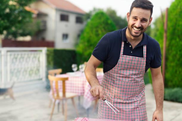 mann, der in seinem hinterhof grill - grillschürze stock-fotos und bilder