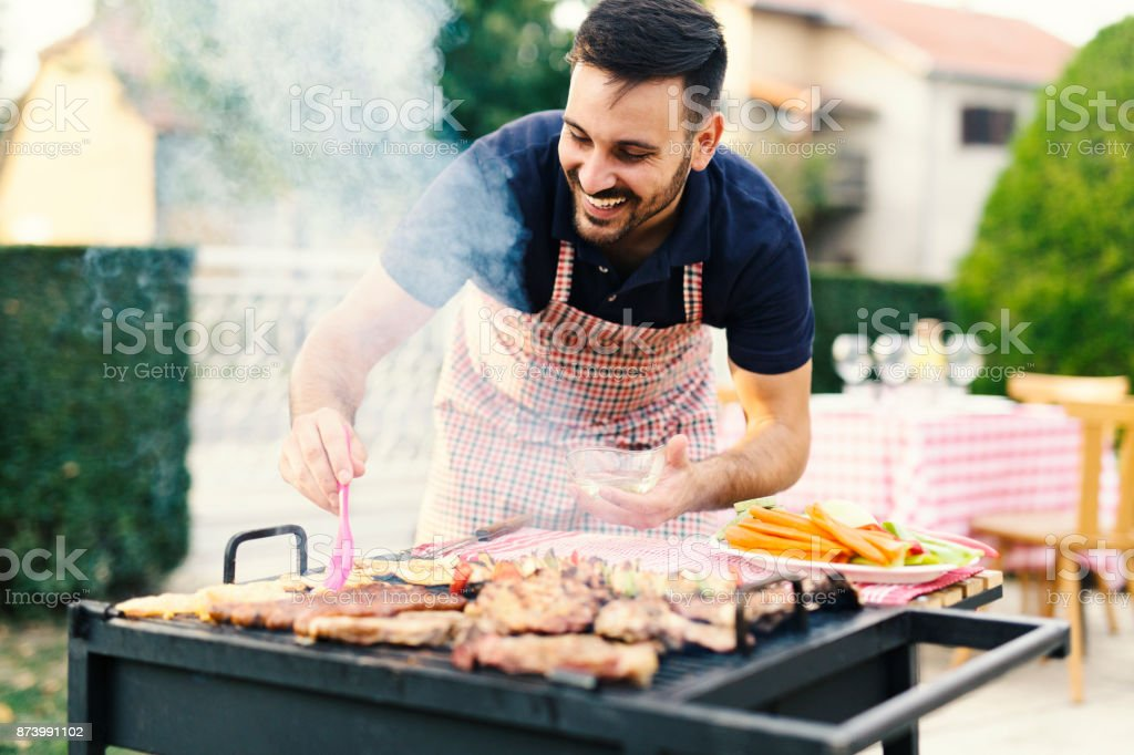 Man making barbecue in his backyard stock photo