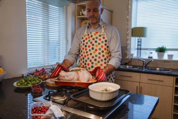hombre haciendo la cena de navidad - padre que se queda en casa fotografías e imágenes de stock