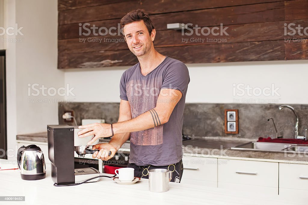 Man making coffee in a modern kitchen stock photo