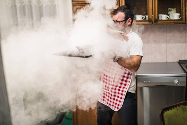 man making dinner - burned oven imagens e fotografias de stock