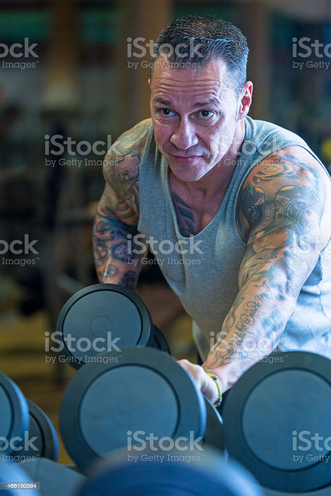 man making dumbbell kickback - workout routine stock photo