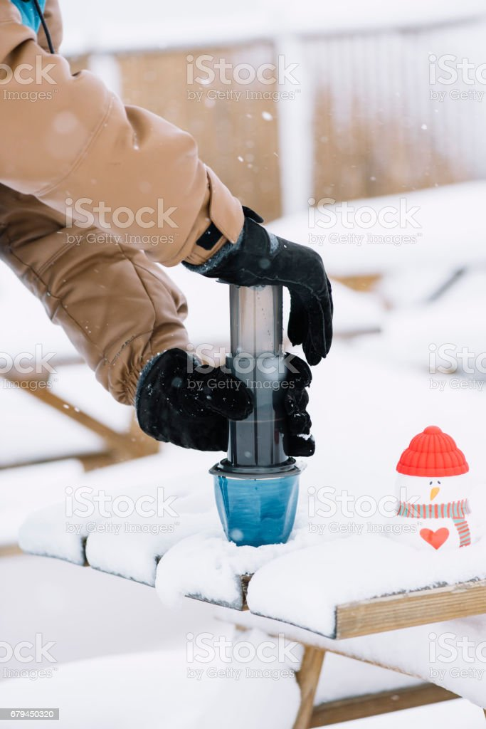 man making fresh aeropressed filter coffee outdoors in the snowfall royalty-free stock photo