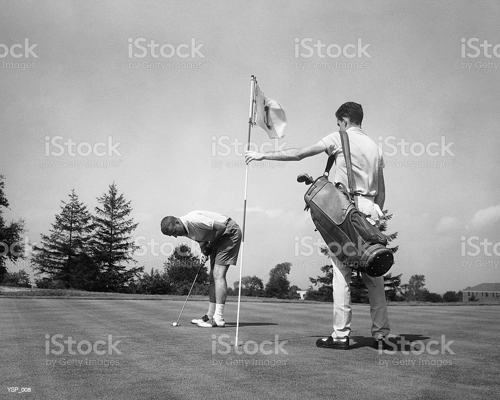 Man making golf shot while caddie stands holding flag royalty-free stock photo