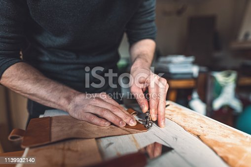 Low angle image of male hands scoring and embossing piece of leather
