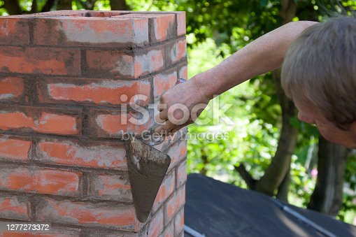istock A man making masonry works, working with a trowel and making a chimney of red bricks 1277273372