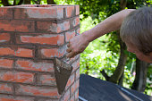A man making masonry works, working with a trowel and making a chimney of red bricks in summer
