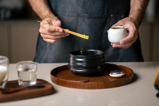 Man making matcha green tea with traditional accessories closeup