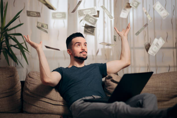 man making money from home on his laptop - throw money away stock pictures, royalty-free photos & images