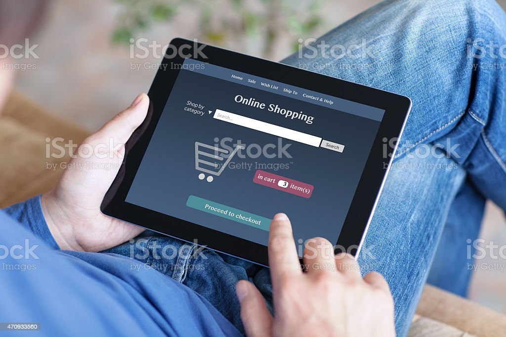 man making online shoppind on a tablet stock photo