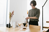 Young man making pour over coffee in the morning.