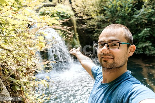 Young man is making personal perspective selfies by the mountain waterfall