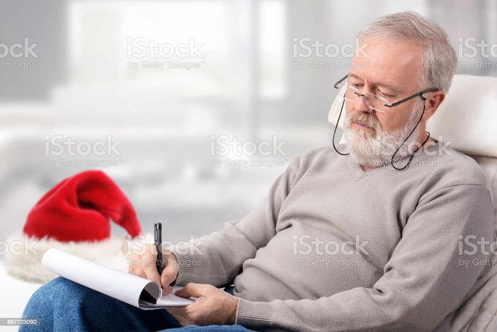 Man making the shopping list for holidays next to a red hat stock photo