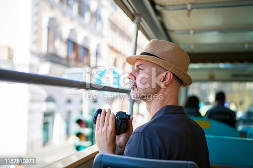 side view portrait 45 years old man with straw hat tourist digital camera in sightseeing bus in euroepan city on sunny summer day, focus on man