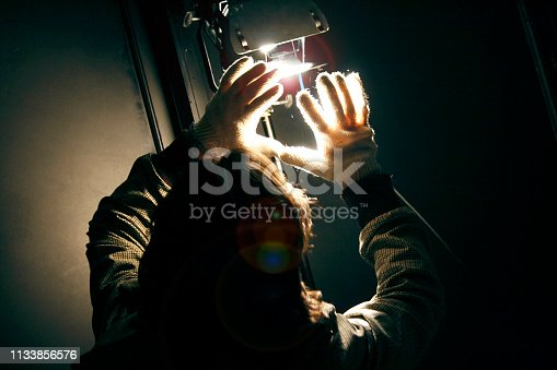 Man manipulating spot light with gloves in production studio for shooting a movie. Reflector and lightening set