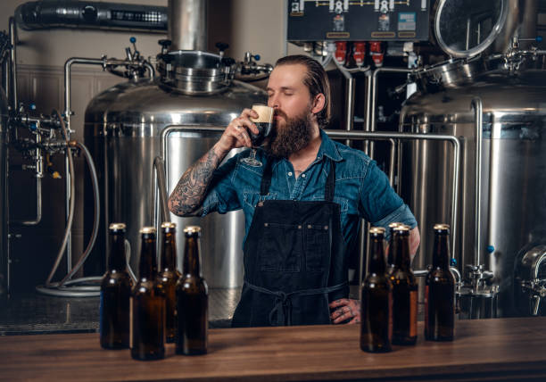 a man manufacturer tasting beer in the microbrewery. - brewery stock pictures, royalty-free photos & images
