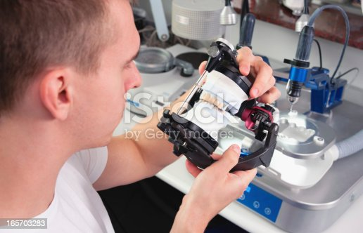 Dental technician manufacturing the dental ceramic crowns. Selective soft focus.