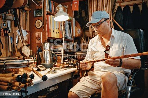 Man manufacturing ney in workshop