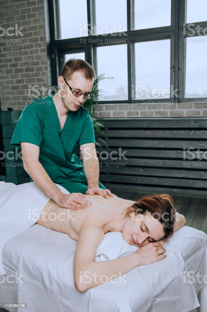 A man massage therapist in glasses and a green uniform massages the...