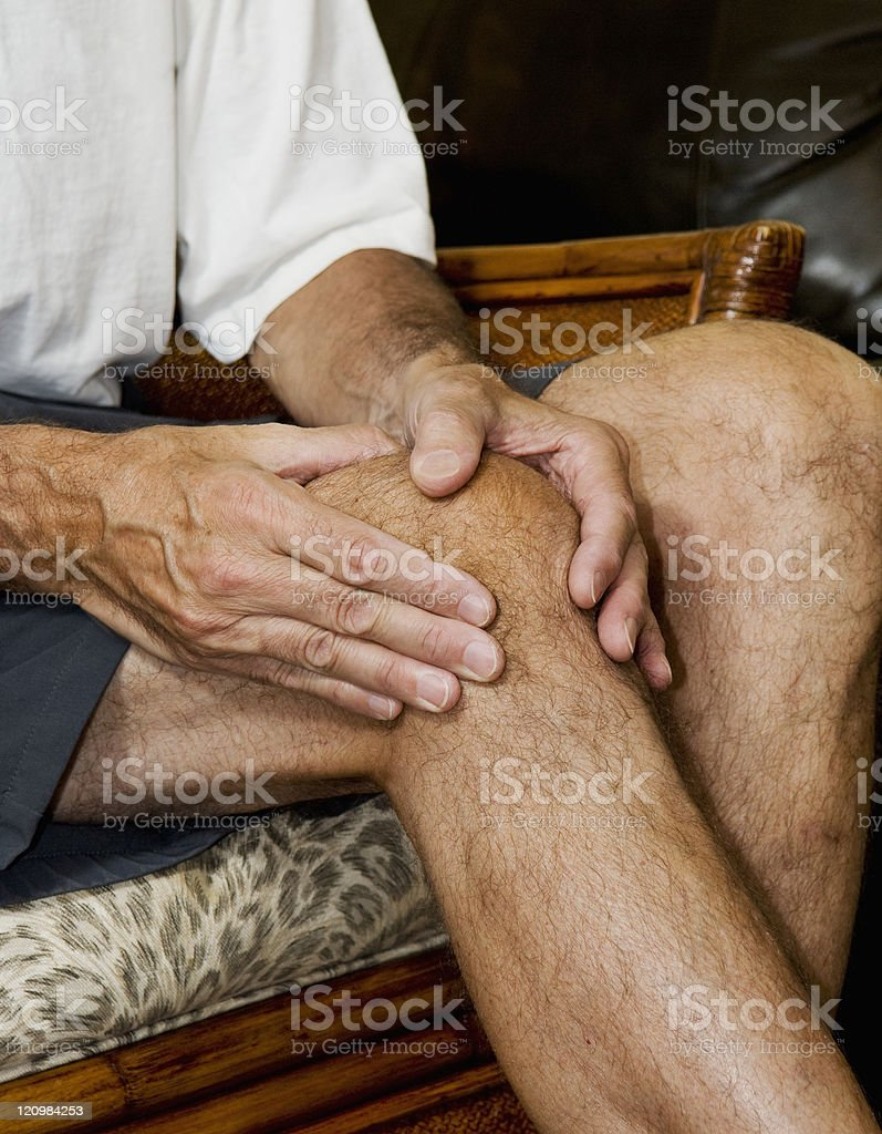 man massaging knee stock photo