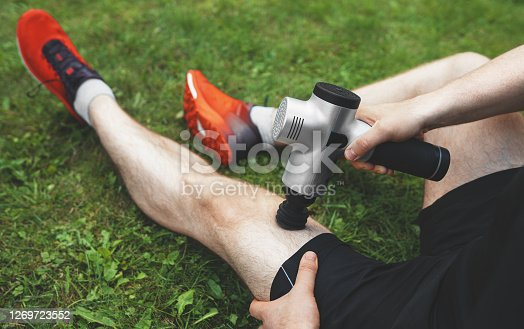 Man massaging leg with massage percussion device after workout.