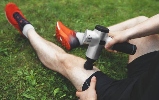 Man massaging leg with massage percussion device after workout. stock photo