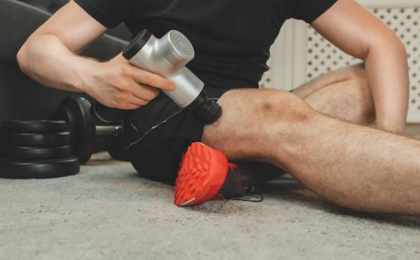 Man massaging leg with massage percussion device. stock photo