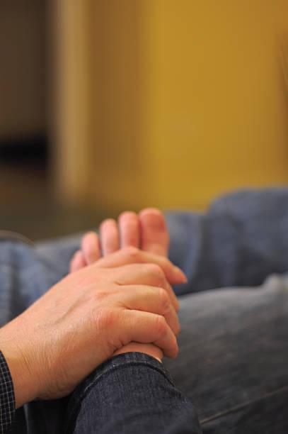 man massaging woman's foot at home stock photo