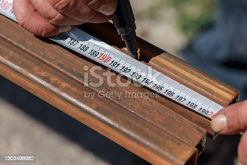 Man master builder measures metal with a working measuring tool, tape measure and marker in the hands of a worker
