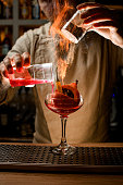 man masterfully add ingredients to cocktail glass with vegetables like pumpkin and pepper inside and makes fire over it