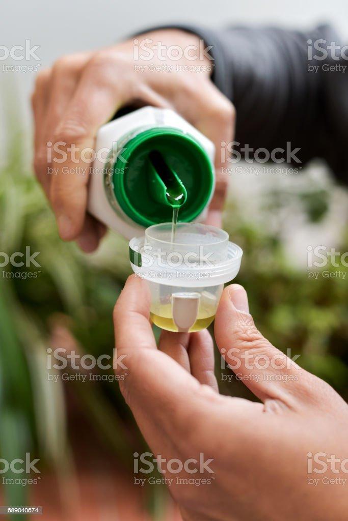 hombre de medir una dosis de abono líquido - foto de stock