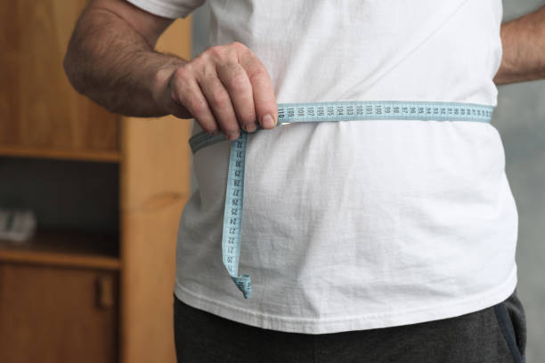 Man measuring his belly with measurement tape standing in the living room. stock photo