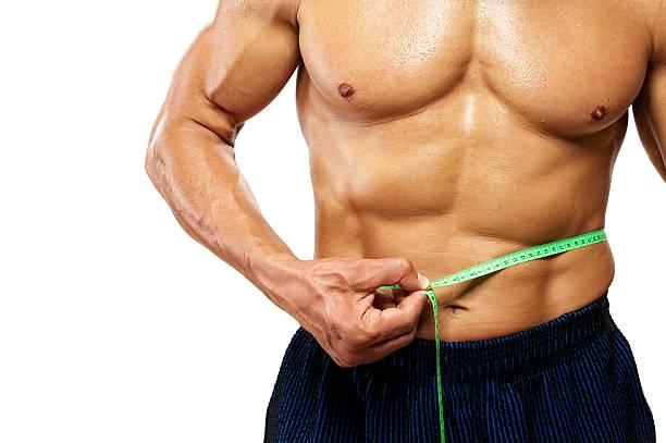 Man measuring his waistline. stock photo