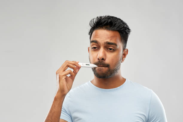 man measuring oral temperature by thermometer stock photo