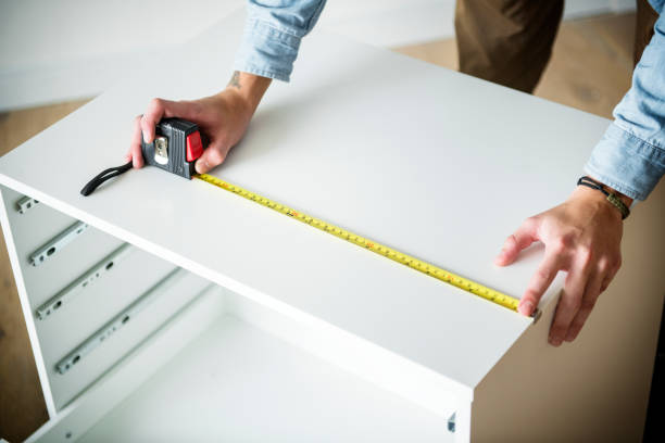 Man measuring the cabinet stock photo