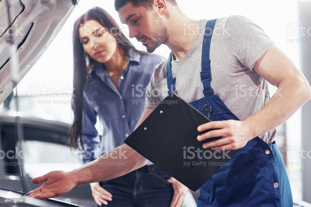 Ein Mann Mechaniker und Frau Kunde schauen Sie sich die Motorhaube und Reparaturen zu diskutieren – Foto