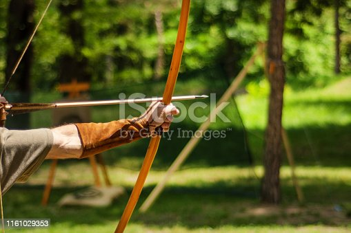 istock Man medieval archer hand holds his bow with an arrow and aiming at the target 1161029353