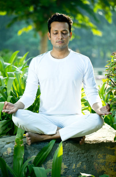 Man meditating in lotus position at park stock photo