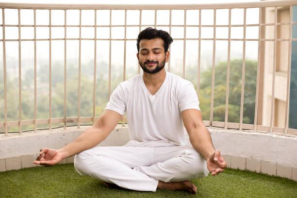 Mann meditiert in Lotus-Position – Foto