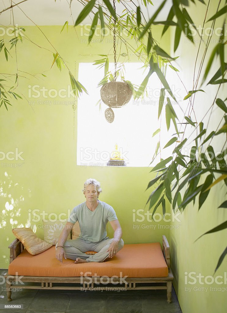Man meditating on patio bench royalty-free stock photo