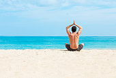 Young man meditating on the white sand beach in Hawaii.