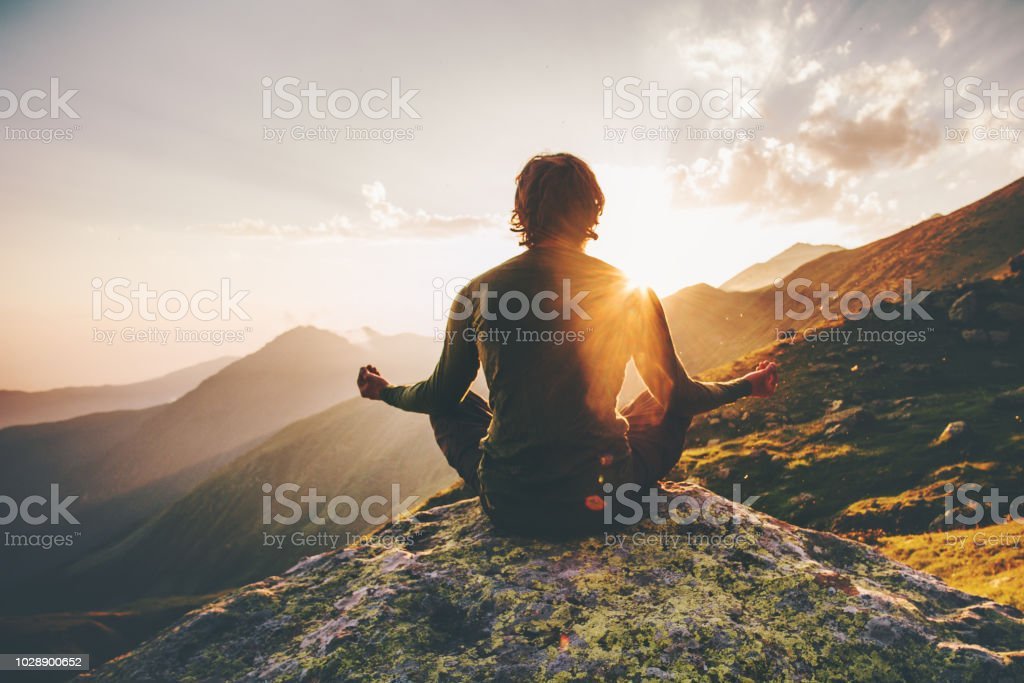 Man meditating yoga at sunset mountains Travel Lifestyle relaxation emotional concept adventure summer vacations outdoor harmony with nature royalty-free stock photo