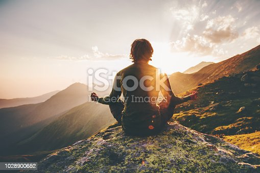 Man meditating yoga at sunset mountains Travel Lifestyle relaxation emotional concept adventure summer vacations outdoor harmony with nature