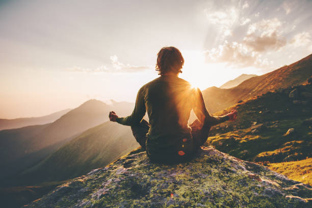 man meditating yoga at sunset mountains travel lifestyle relaxation emotional concept adventure summer vacations outdoor harmony with nature - yoga stock photos and pictures